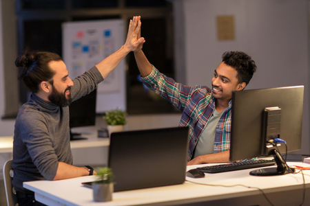 creative team making high five at night office Фото со стока