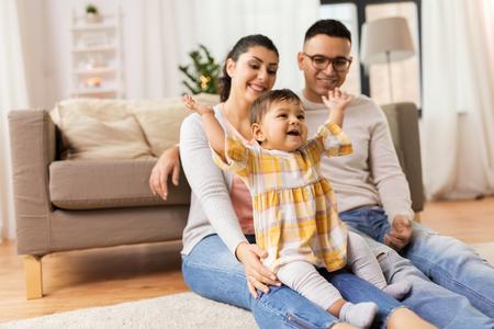 gelukkige familie en baby dochter thuis spelen
