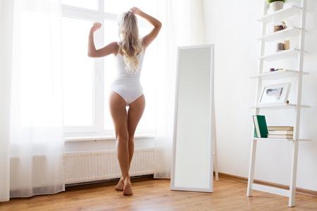 woman in underwear at window in morning