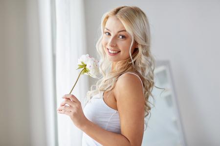 Vrouw in ondergoed ruikende bloem op venster Stockfoto - 96033519