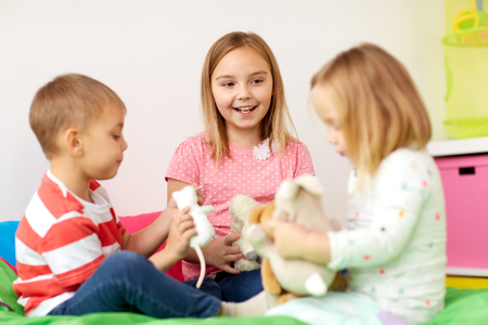 happy kids playing with plush toys at home