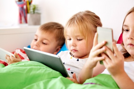 little kids with tablet pc in bed at home Stock Photo