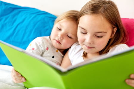 little girls or sisters reading book in bed