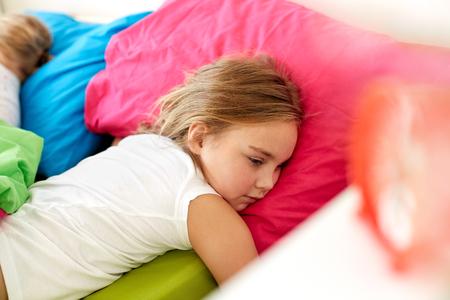little girl lying awake in bed at home Stockfoto