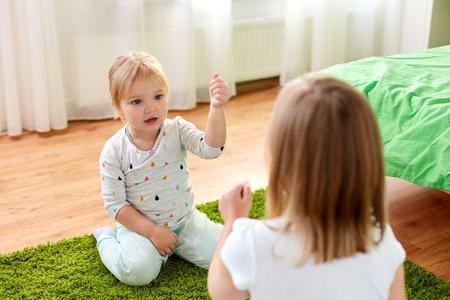 girls playing rock-paper-scissors game at home 版權商用圖片