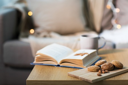 oat cookies, almonds and book on table at home