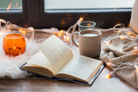 book and coffee or hot chocolate on window sill Stockfoto