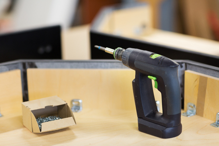 screwdriver with screws and furniture at workshop