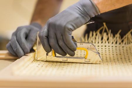 assembler with staple gun making furniture