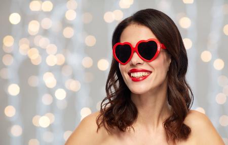 Frau mit rotem Lippenstift und Herz formte Schattierungen Standard-Bild - 96348073