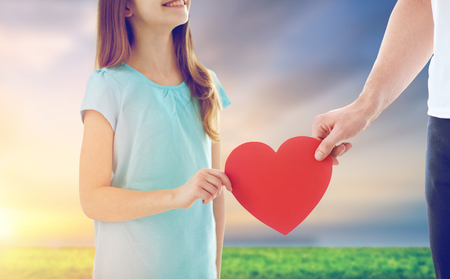 close up of daughter and father holding red heart