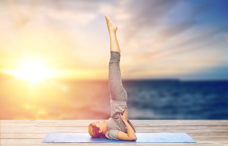 woman doing yoga in shoulderstand pose on mat Stock Photo - 96495897