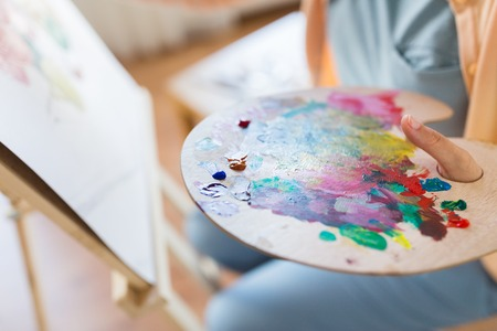 artist with paint palette painting at art studio