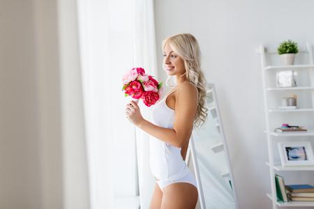 窓に花束を持つ下着の女性