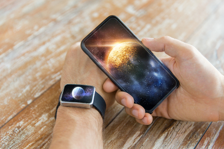 close up of hands with smartphone and smart watch