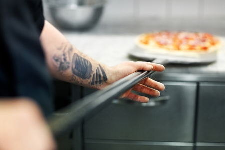 cook or baker hand with pizza on peel at pizzeria Banque d'images