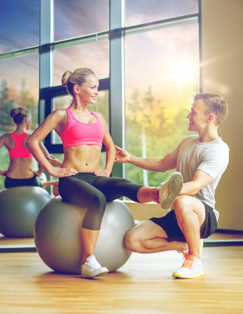 smiling man and woman with exercise ball in gym Stock Photo