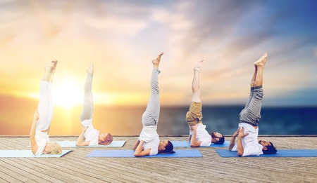 people doing yoga shoulderstand on mat outdoors Stock Photo - 96778846