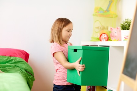 happy little girl with toy box at home