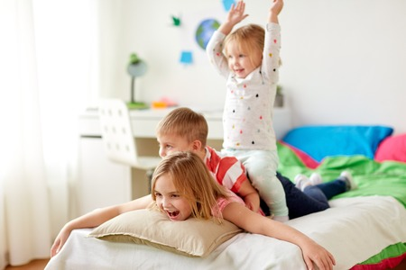 happy little kids having fun in bed at home