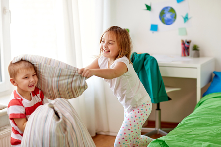 kids playing and fighting by pillows at home Stockfoto