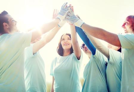 group of happy volunteers making high five in park