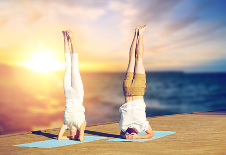 couple doing yoga headstand on mat outdoors