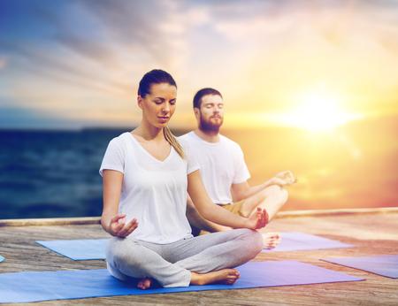 people meditating in yoga lotus pose outdoors 版權商用圖片