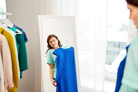 pensive plus size woman with blue dress at mirror