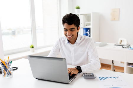 businessman with laptop and papers at office