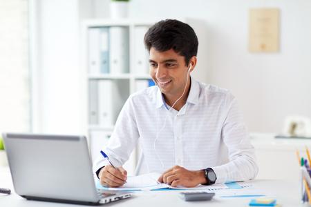 businessman in earphones working at office