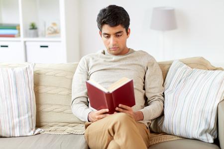 ソバに座って家で本を読む男