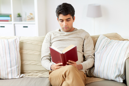 man sitting on sofa and reading book at home Stockfoto