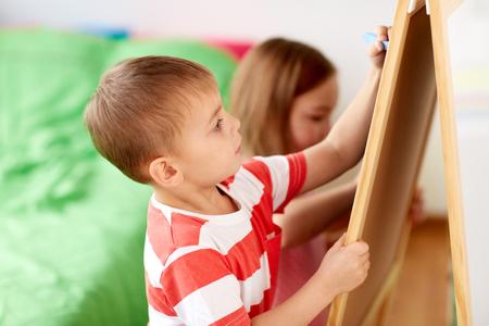 happy kids drawing on chalk board at home 版權商用圖片