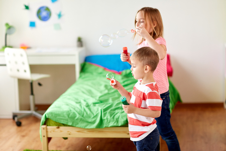 kids blowing soap bubbles and playing at home 版權商用圖片