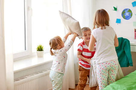 kids playing and fighting by pillows at home 版權商用圖片