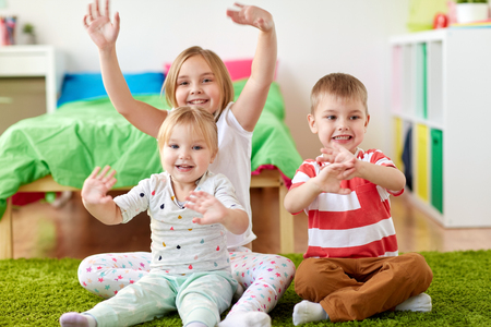 group of happy kids sitting on floor at home