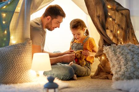 自宅で子供のテントでおもちゃで遊ぶ幸せな家族 写真素材