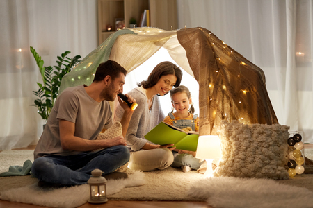 happy family reading book in kids tent at home Standard-Bild