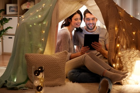 happy couple with tablet pc in kids tent at home Stok Fotoğraf