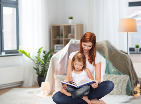 happy mother with little daughter reading book