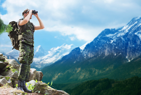 soldier with backpack looking to binocular