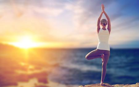 happy woman making yoga tree pose over sea