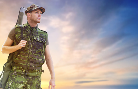 young soldier or hunter with gun over sky Standard-Bild