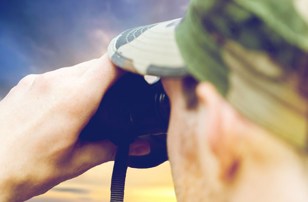 close up of soldier looking to binocular