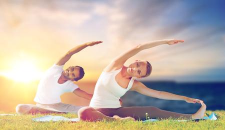 couple making yoga exercises outdoors Standard-Bild