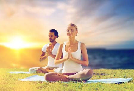 happy couple making yoga and meditating outdoors Standard-Bild