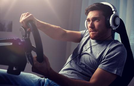 man playing car racing video game at home Standard-Bild