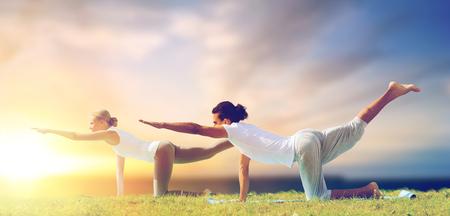 couple making yoga balancing table pose outdoors Standard-Bild