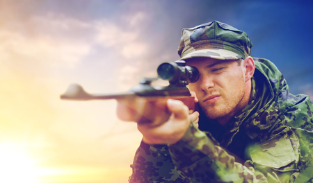 soldier or hunter with gun aiming and shooting
